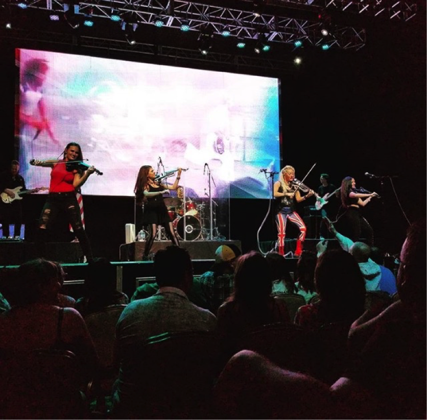 The full band from left to right: John Wedemeyer (guitar), Carissa Werner (5 string violin), Christina Reigert (5 string violin), Michael Licata (drums), Nina DiGregorio Licata (5 string violin), Michael Kelly (bass), Chandra Meibalane (5 string violin)